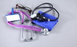 Stéthoscope, coeur rouge, verres et mètre de tension artérielle sur le fond blanc Foyer sélectif Images libres de droits