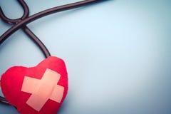 Stéthoscope de soins de santé et de médecine et symbole rouge de coeur concept sain et de santé du monde d'assurance de jour Images libres de droits