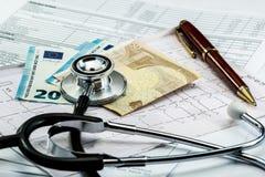 Stéthoscope et argent sur l'électrocardiogramme Euro Photographie stock