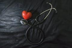 Stéthoscope et chiffre rouge de coeur sur le fond noir, d'intérieur images stock