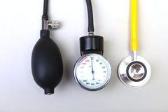 Stéthoscope et mètre médicaux de tension artérielle sur le fond blanc Soins de santé Photos stock