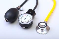 Stéthoscope et mètre médicaux de tension artérielle sur le fond blanc Soins de santé Image libre de droits