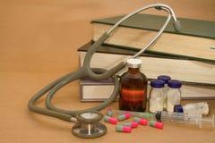 Stéthoscope et médicaments sur le livre Photographie stock libre de droits