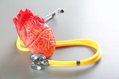 Stéthoscope et modèle de coeur sur le concept gris de crise cardiaque de fond Images stock