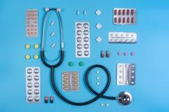 Stéthoscope et pilules dans des boursouflures sur un fond bleu image stock