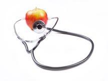 Stéthoscope et pomme au-dessus du fond blanc Photographie stock libre de droits