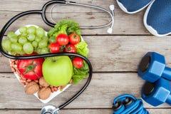 Stéthoscope, légumes et fruits organiques et équipement de sport sur la surface en bois, concept sain de mode de vie Photo stock