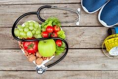 Stéthoscope, légumes organiques et bande de fruits et de mesure sur la surface en bois, concept sain de mode de vie Image stock