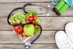 Stéthoscope, légumes organiques et fruits, espadrilles, corde à sauter sur la surface en bois, concept sain de mode de vie Image libre de droits