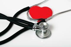 Stéthoscope médical et un coeur rouge Photographie stock