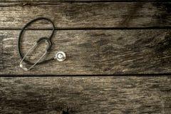 Stéthoscope médical noir se trouvant sur les planches en bois texturisées âgées images libres de droits