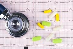 Stéthoscope médical se trouvant sur le diagramme de cardiogramme avec la pile des pilules Prévention et aide de protection sanita Images libres de droits