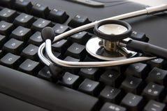 Stéthoscope par un clavier d'ordinateur photographie stock libre de droits