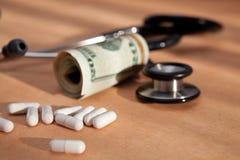 Stéthoscope, pillules médicales et dollar US Images stock