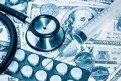 Stéthoscope, pilules, seringue au-dessus d'une pile de dollars Images libres de droits