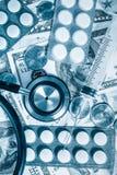 Stéthoscope, pilules, seringue au-dessus d'une pile de dollars Photographie stock libre de droits
