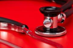 Stéthoscope, plan rapproché, fond rouge photographie stock libre de droits