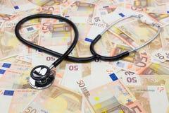 Stéthoscope professionnel noir se trouvant sur beaucoup d'euro notes Photos libres de droits