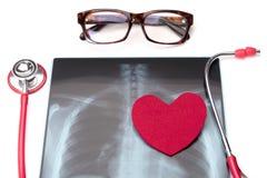 Stéthoscope rouge de soins de santé et de médecine de jour de santé du monde et symbole rouge de coeur sur le film radiographique Images libres de droits