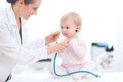 Stéthoscope s'usant de chéri de docteur pédiatrique photo stock