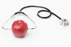 Stéthoscope s'usant de pomme rouge au-dessus de blanc Photos libres de droits