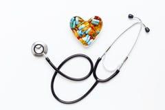 Stéthoscope sur le fond blanc avec des pilules dans la forme du coeur Photographie stock