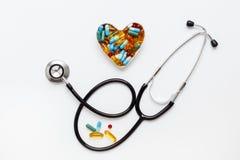 Stéthoscope sur le fond blanc avec des pilules dans la forme du coeur Images stock