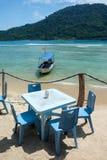 Stół i cztery krzesła z łodzią na tropikalnej wyspie wyrzucać na brzeg obrazy royalty free