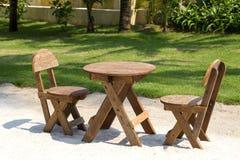 Stół i drewniani krzesła w tropikalnym ogródzie obok morza na piasek plaży, Tajlandia z bliska Zdjęcie Stock