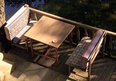 Stół i dwa ławki z filiżanką, blisko do wody obraz stock