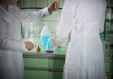 Stół pełno substancje chemiczne i kolby laboratorium chemicznego Dwa kobieta w medycznych togach zdjęcie stock