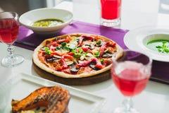 Stół w kawiarni z jarskimi naczyniami pizza, napoje -, piec na grillu bani, kulebiaka i cukierki, zdjęcie royalty free