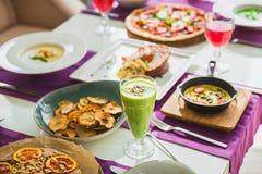 Stół w kawiarni z jarskimi naczyniami pizza, sałatki, kulebiak z cytrusem i napój -, zdjęcia royalty free