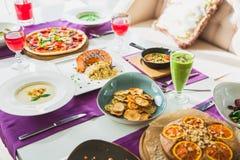 Stół w kawiarni z jarskimi naczyniami pizza, sałatki, kulebiak i napoje -, Jedzenie w restauraci obrazy stock
