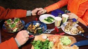 Stół z jedzeniem w drewnach na tle potomstwo pary mienia ręki, zbiory wideo