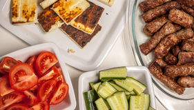 Stół z piec na grillu cevapcici pomidorami i ogórkami obraz stock