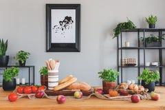 Stół z pomidorami, chlebem, jabłkami i ziele w rustical jadalni wnętrzu, obrazy royalty free