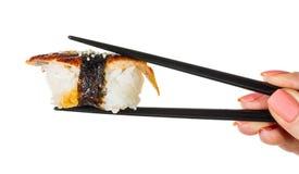 Stöcke halten Sushi mit Aal Stockfoto