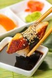 Stöcke halten Sushi mit Aal in der Sojasoße Stockfotos
