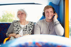 Störande passagerare för man på bussresa med hög musik royaltyfri bild