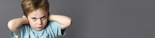 Störrisches Kind mit Haltung das Elternschelten, Ohren blockierend ignorierend, Panorama Stockfotografie