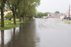 Störtfloden täcker gatan i vatten Arkivfoton