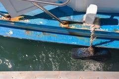 Stötsäker sida av fiskebåten DIY vid det gamla gummihjulet Royaltyfri Foto