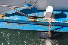 Stötsäker sida av fiskebåten DIY vid det gamla gummihjulet Royaltyfria Foton