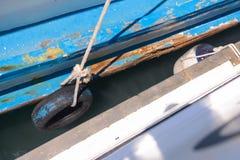 Stötsäker sida av fiskebåten DIY vid det gamla gummihjulet Royaltyfria Bilder