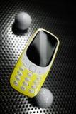 Stötsäker telefon på metallyttersida med golfbollar Arkivbild