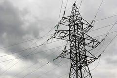 Stötta kraftledningar och trådar mot den stormiga himlen royaltyfria bilder