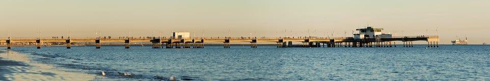 stöttar den långa panorama- pir för strandbelmont solnedgång Royaltyfri Bild