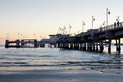 stöttar den långa pir för strandbelmont solnedgång Arkivfoton