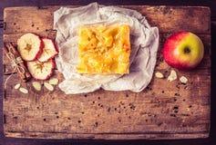 Stück Apfelkuchen mit Zimt und Mandeln auf einer dunklen Holzkiste Stockbild